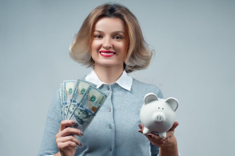 Концепция сбережений Женщина держа копилку и пук банкнот денег стоковые изображения rf