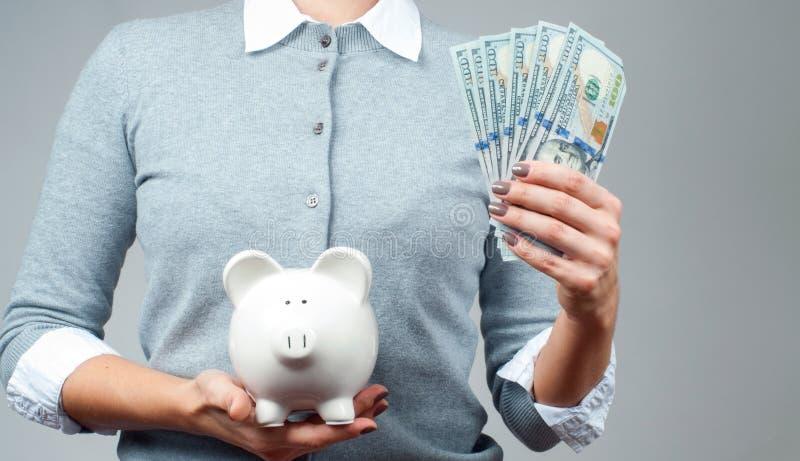 Концепция сбережений Женщина держа копилку и пук банкнот денег стоковое фото