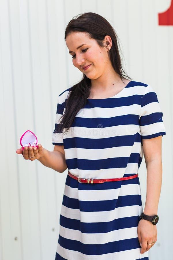 Концепция свадьбы, влюбленности, захвата и счастья - усмехаясь женщина в striped платье держа розовую подарочную коробку с кольцо стоковое изображение rf