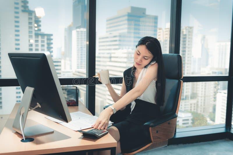 Концепция связи технологии, портрет привлекательной бизнес-леди вызывает на мобильном телефоне пока работающ на ее рабочем столе  стоковые изображения