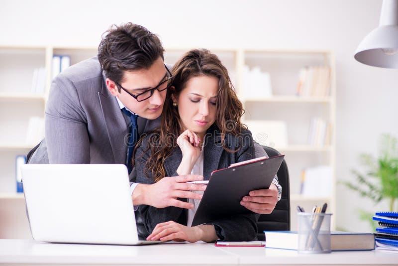Концепция сексуальных домогательств с человеком и женщиной в офисе стоковое фото rf