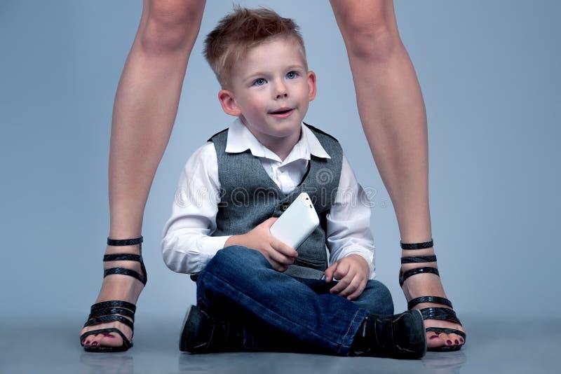 Концепция семьи высоких пяток Стильный ребёнок стоя с его fa стоковые изображения