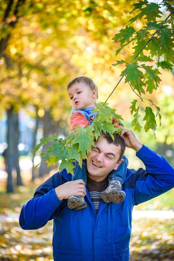 Концепция семьи, детства и отцовства счастливый носить отца стоковое изображение