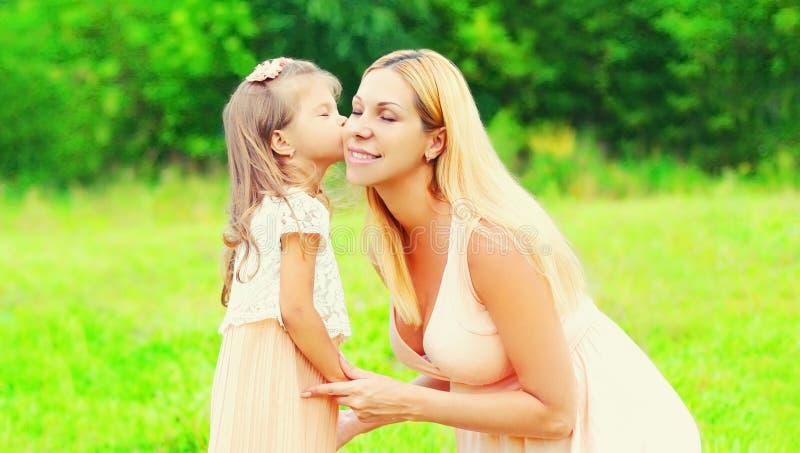 Концепция семьи - ребенок дочери портрета счастливый маленький целуя мать летом стоковое фото