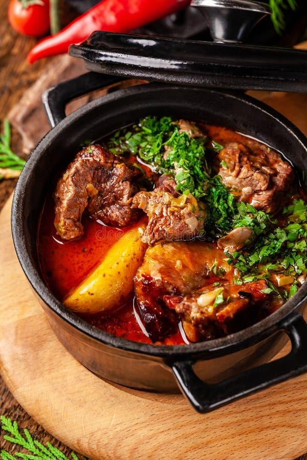 Концепция сербской кухни Сочная испеченная говядина в своем собственном соке с картошками, овощами и зелеными цветами Подача в ог стоковые изображения