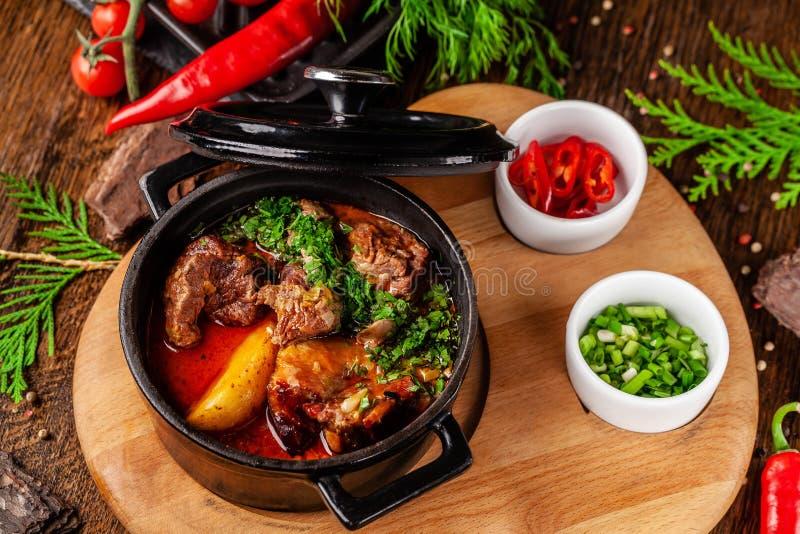 Концепция сербской кухни Сочная испеченная говядина в своем собственном соке с картошками, овощами и зелеными цветами Подача в ог стоковое фото