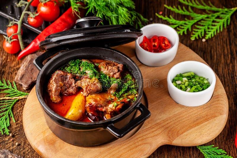 Концепция сербской кухни Сочная испеченная говядина в своем собственном соке с картошками, овощами и зелеными цветами Подача в ог стоковые фото