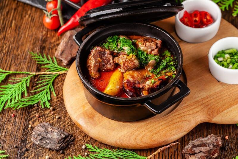 Концепция сербской кухни Сочная испеченная говядина в своем собственном соке с картошками, овощами и зелеными цветами Подача в ог стоковая фотография