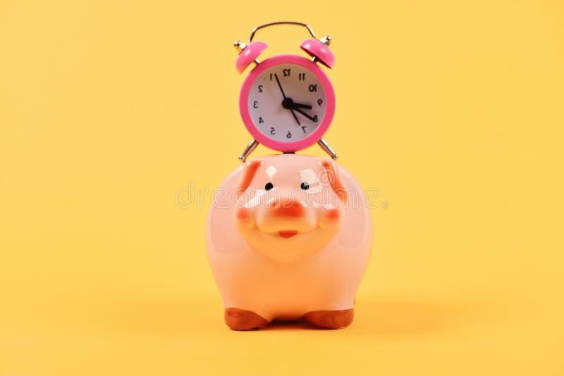 Концепция спасения времени Розовая копилка с секундомером на верхней части стоковые изображения