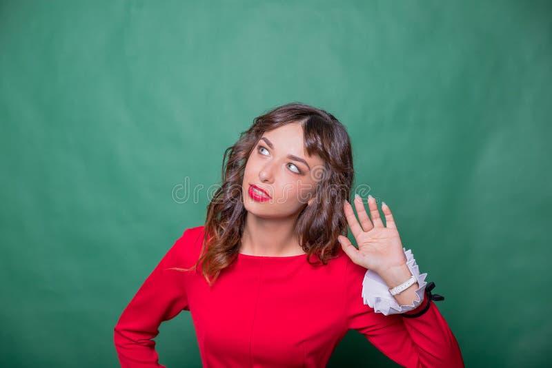 Концепция сплетни Красочный портрет студии милой молодой женщины с ладонью около ее уха милая женщина в красных владениях платья стоковые изображения