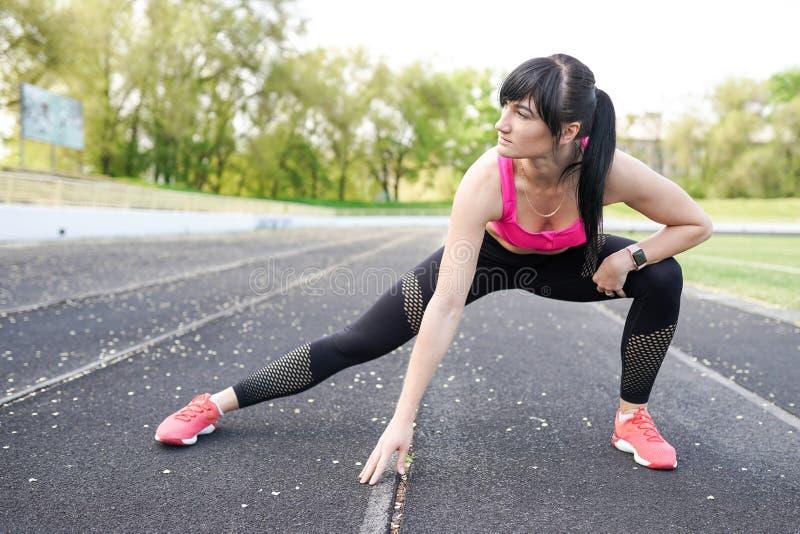 Концепция спорта и образа жизни - женщина делая спорт outdoors стоковая фотография rf