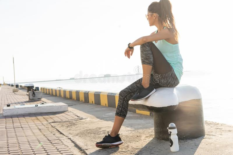 Концепция спорта и образа жизни - женщина отдыхая после делать резвится outdoors стоковое фото rf