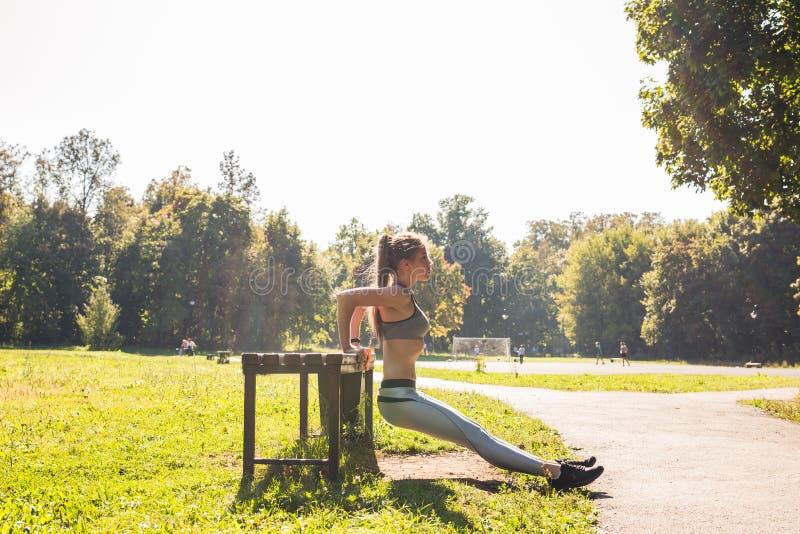 Концепция спорта, фитнеса, тренировки и образа жизни - женщина делая спорт outdoors стоковое фото rf