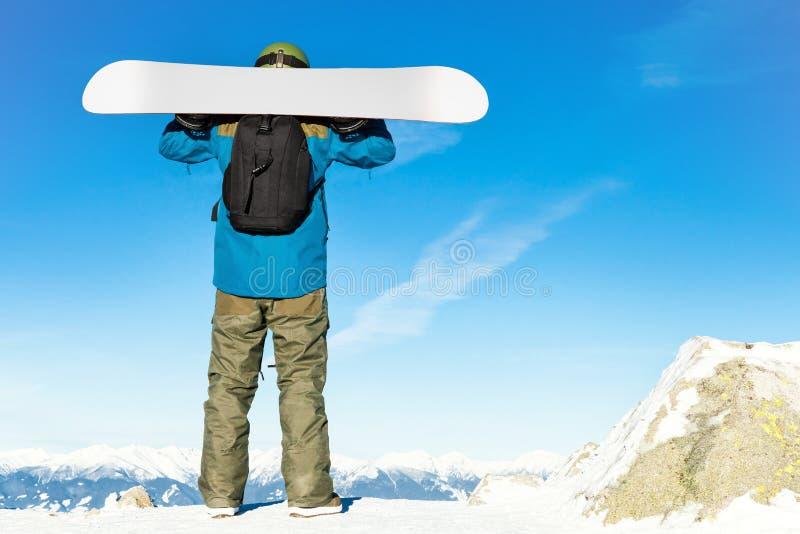 Концепция спорт зимы - мужской snowboarder держа его сноуборд на его плечах вверху гора и наслаждаясь пейзажем стоковая фотография rf