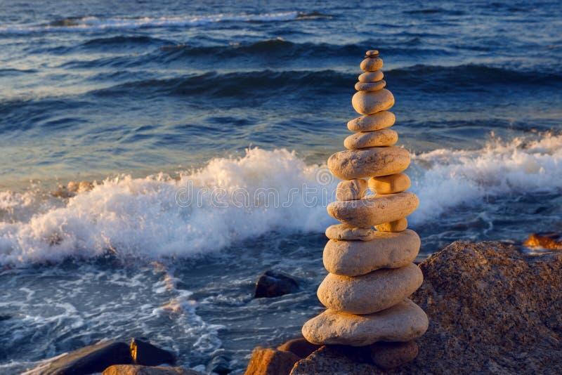 Концепция сработанности и баланса Дзэн утеса на заходе солнца Камни баланса и пуаза против моря стоковая фотография