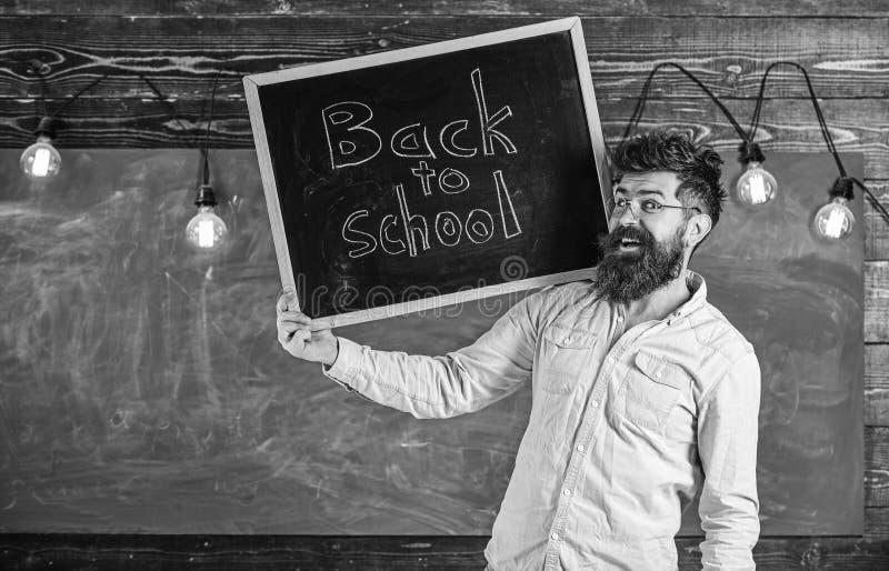 Концепция средней школы Человек с бородой и усик на жизнерадостных студентах гостеприимсв стороны, доска на предпосылке Учитель стоковые фото