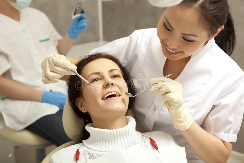 Концепция стоматологии - дантист с зеркалом проверяя терпеливую девушку стоковая фотография rf
