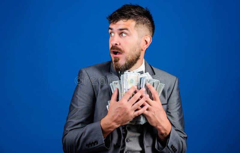 Концепция сюрприза заработков Денег кучи владением бизнесмена человека предпосылка бородатых голубая Удивленный бизнесмен чувству стоковое изображение rf
