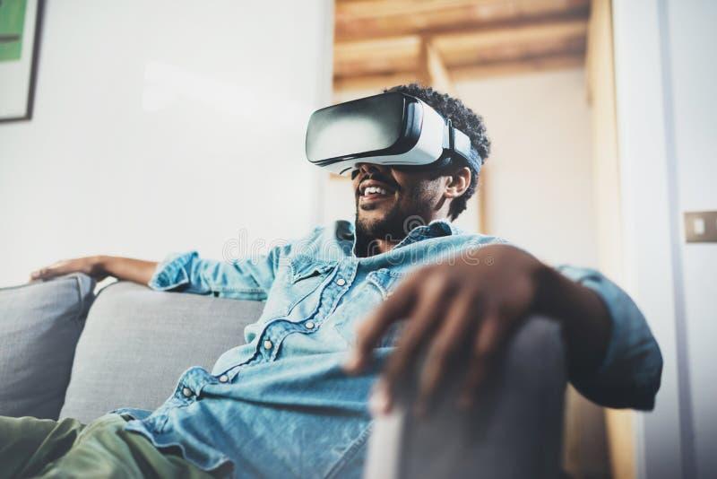 Концепция технологии, игры, развлечений и людей Молодой африканский человек наслаждаясь шлемофоном стекел виртуальной реальности  стоковая фотография rf