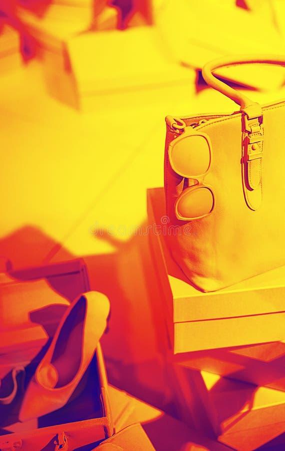 Концепция ультрамодных женских аксессуаров кладет в мешки, солнечные очки, ботинки на пустых коробках и красная желтая предпосылк стоковые изображения rf