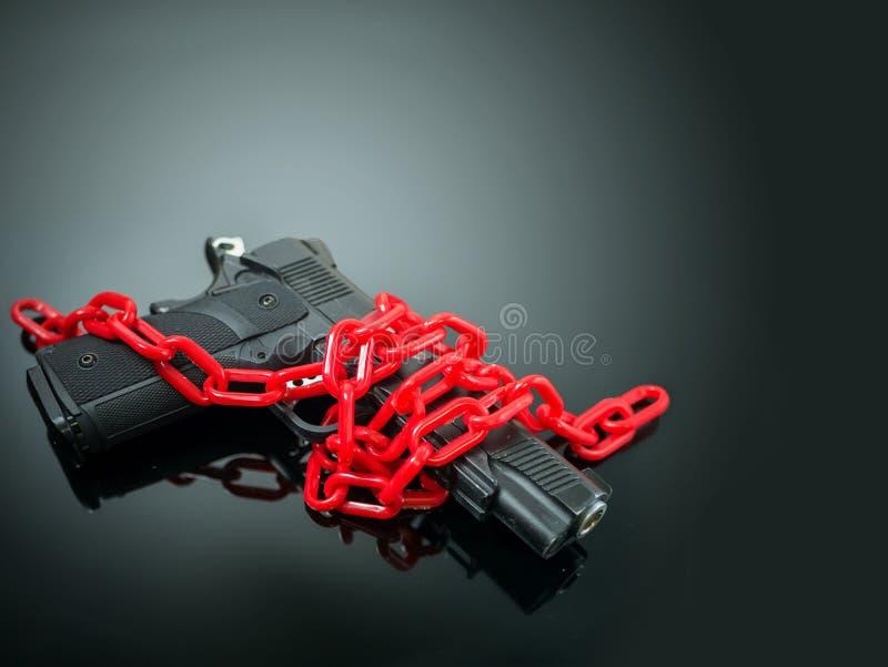 Концепция управления орудием реформы красная цепь вокруг личного огнестрельного оружия на черном bg стоковые фото