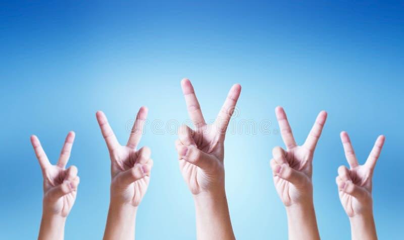 Концепция успеха: Рука делая жест номера два на голубой предпосылке стоковое фото rf