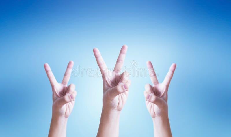 Концепция успеха: рука делая жест номера два на голубой предпосылке стоковое изображение
