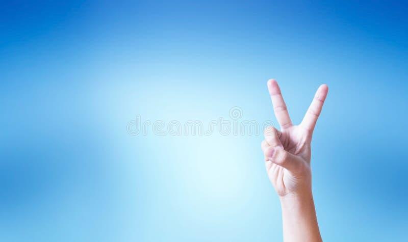 Концепция успеха: рука делая жест номера два на голубой предпосылке стоковые изображения rf