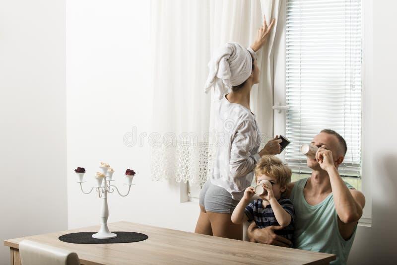 Концепция утра по заведенному порядку Мать и отец и ребенок сидят на таблице в утре Счастливая семья потратить время совместно, б стоковое изображение