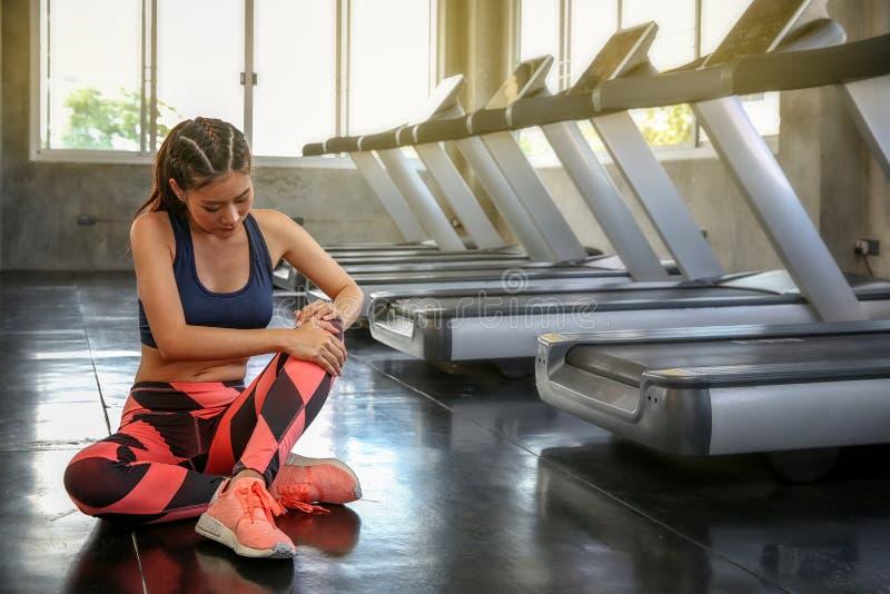 Концепция ушиба спорт Женщины боль колена от неправильной тренировки девушка спортсмена массажируя болея мышцы бедренной кости чу стоковые изображения rf