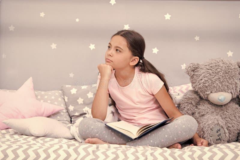 Концепция фантазера Милый маленький фантазер Мечта девушки фантазера в кровати Фантазер ребенка с книгой и плюшевым мишкой Мечта  стоковые изображения rf