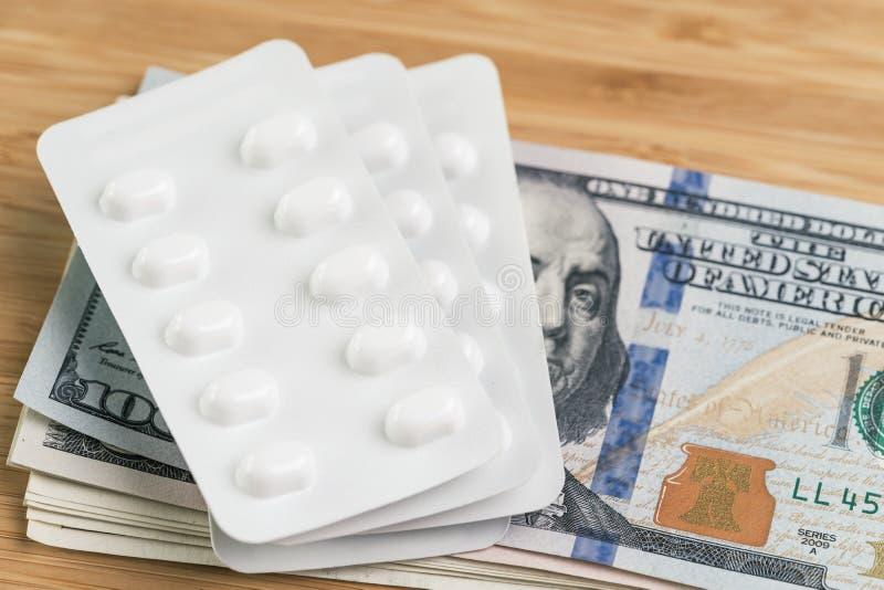 Концепция фармации, здравоохранения или медицинских расходов, белый пакет таблеток на куче денег банкнот доллара США стоковое изображение