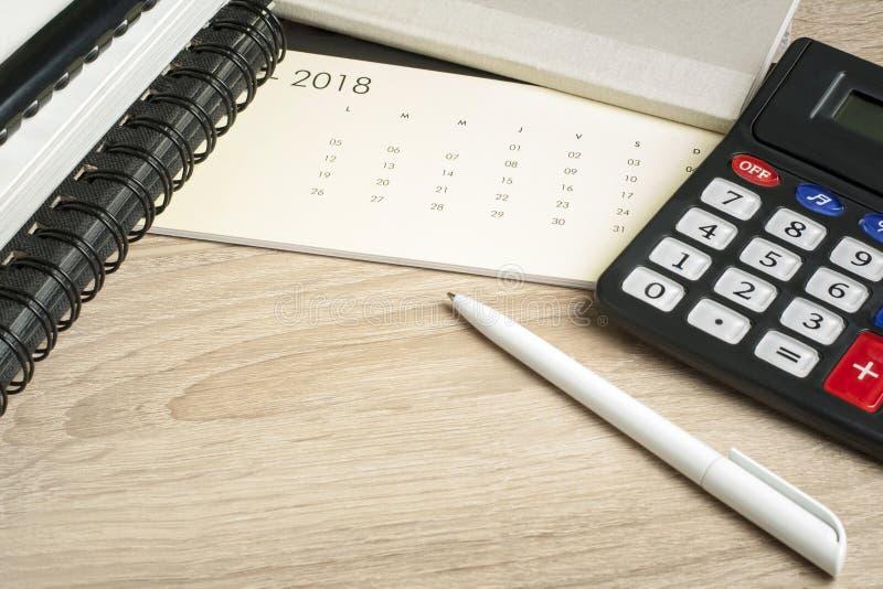 Концепция финансовых и бюджета Счетнаяа книга, калькулятор, ручка и календарь на таблице офиса стоковые изображения