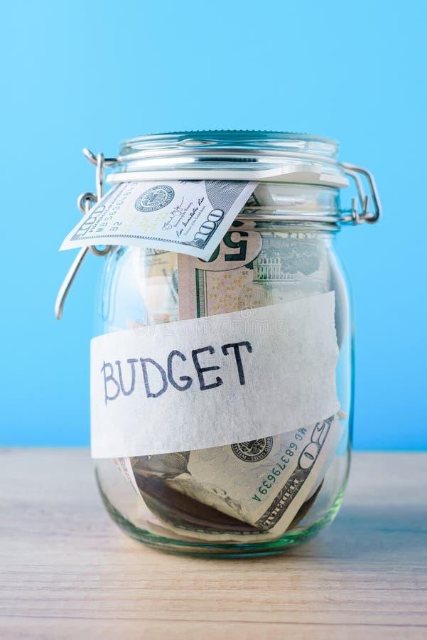 Концепция финансов и вклада Стеклянный банк сохранения с долларовыми банкнотами и бюджет надписи на голубой предпосылке стоковые фотографии rf
