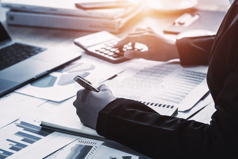 концепция финансов учета коммерческих операций бухгалтер используя калькулятор для высчитывает с деятельностью ноутбука в офисе стоковые фото