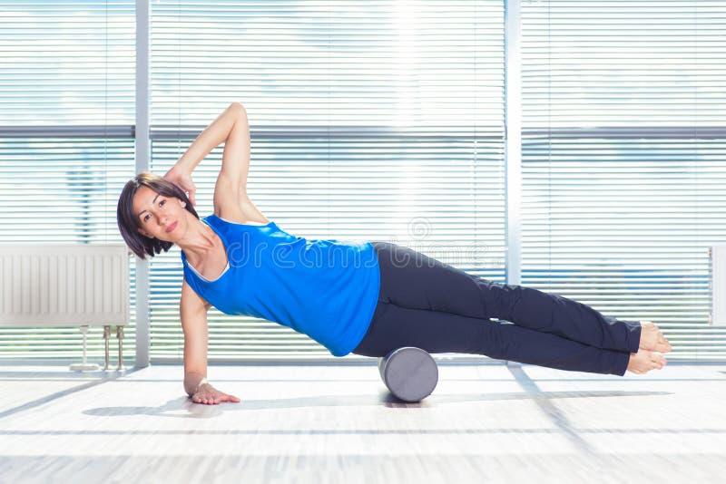 Концепция фитнеса, спорта, тренировки и образа жизни - женщина делая pilates на поле с роликом пены стоковая фотография rf