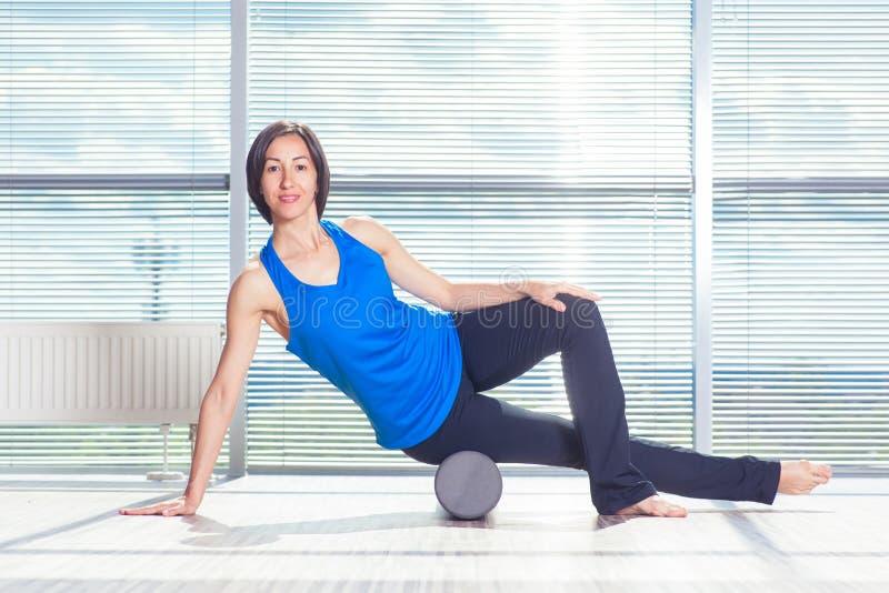 Концепция фитнеса, спорта, тренировки и образа жизни - женщина делая pilates на поле с роликом пены стоковые фотографии rf