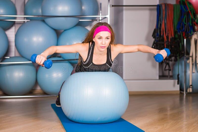 Концепция фитнеса, спорта, тренировки и образа жизни - усмехаясь женщина с гантелями и шарик тренировки в спортзале стоковая фотография rf