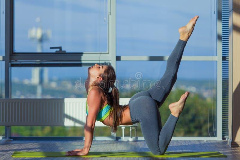 Концепция фитнеса, спорта, тренировки и образа жизни - усмехаясь женщина протягивая на циновке в спортзале свет от большого окна стоковая фотография