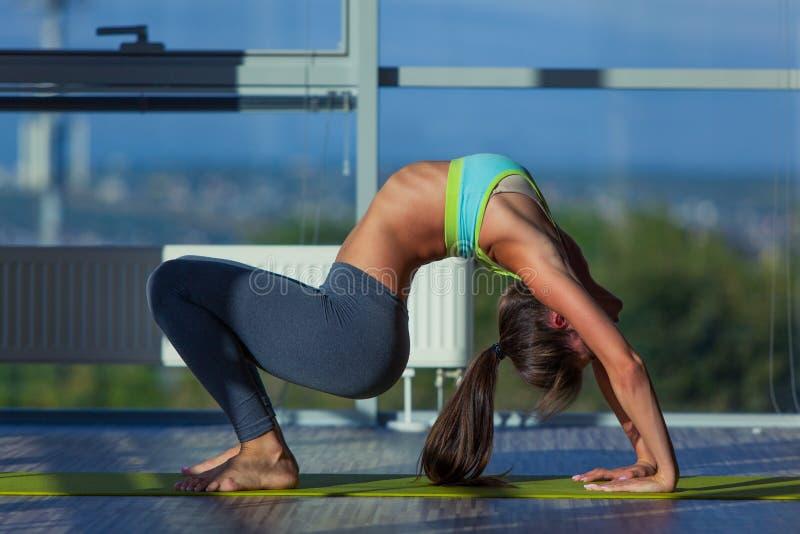 Концепция фитнеса, спорта, тренировки и образа жизни - усмехаясь женщина протягивая на циновке в спортзале свет от большого окна стоковое изображение