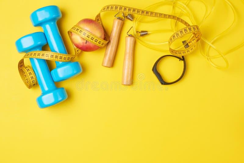 Концепция фитнеса с голубыми гантелями, веревочкой скачки и отслежывателем на желтой предпосылке, положением фитнеса взгляда свер стоковые фотографии rf