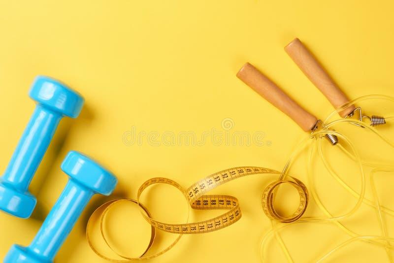 Концепция фитнеса с голубыми гантелями, измеряя лентой и веревочкой скачки на желтой предпосылке Взгляд сверху с космосом экземпл стоковые фото