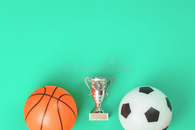 Концепция футбола и баскетбола с шариками и чашкой стоковое изображение rf
