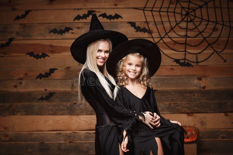 Концепция хеллоуина - жизнерадостная мать и ее дочь в костюмах ведьмы празднуя хеллоуин представляя с изогнутыми тыквами над лету стоковые фотографии rf