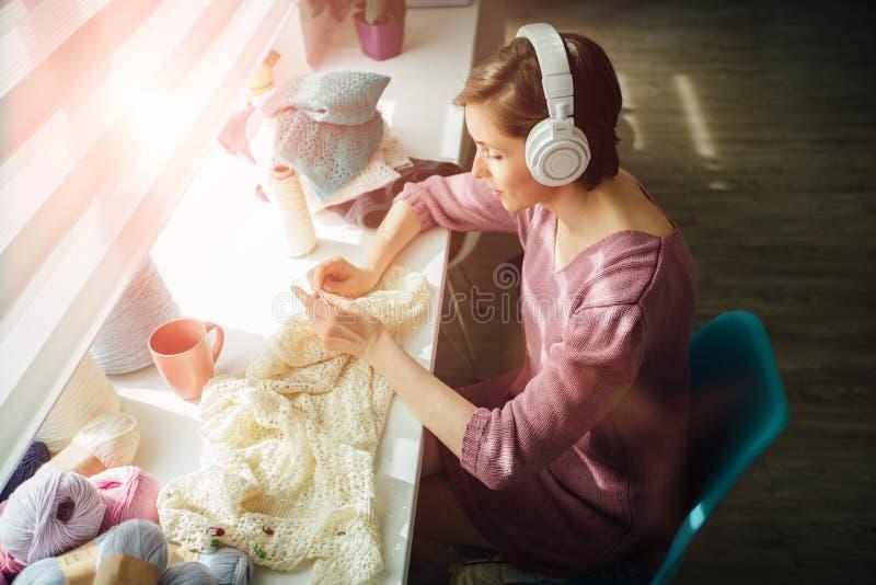Концепция хобби, настроения и отдыха Женщина ослабляя с наушниками пока вяжущ нежное платье с вязанием крючком в солнечном дне r стоковая фотография rf