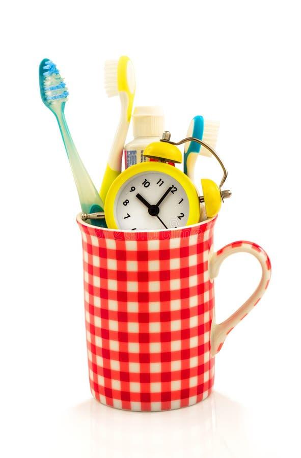 Концепция чашки с зубной щеткой, зубной пастой, будильником стоковая фотография rf