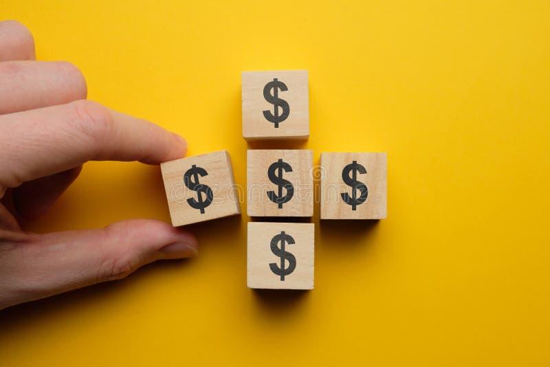 концепция экономии денег и экономии - деревянные кубики с долларовым знаком с рукой стоковые фото
