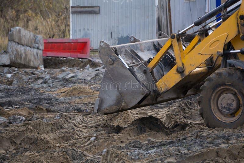 Концепция agronomy, желтый трактор с ведром демонстрирует работу стоковая фотография rf