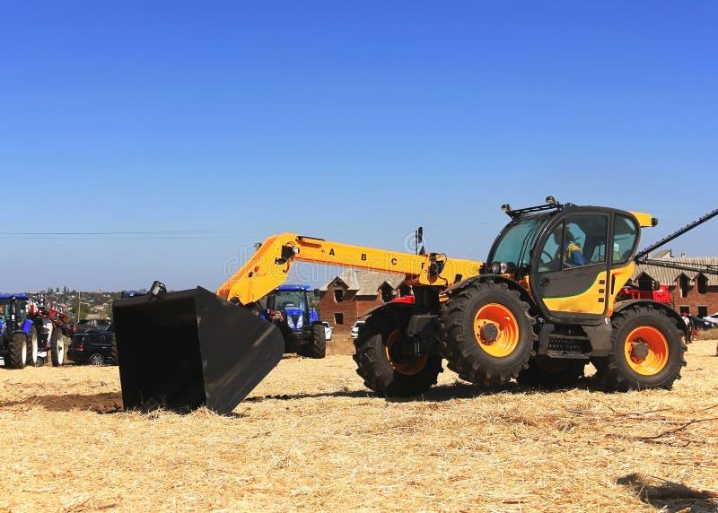 Концепция agronomy, желтый трактор с demonstr ведра стоковое изображение