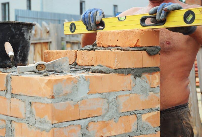 Концепция Bricklaying каменщика Инструменты Bricklaying Каменщик используя уровень для того чтобы проверить его стену конструкции стоковое изображение rf
